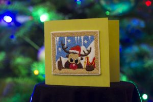 Embroidered Reindeer stick to card.